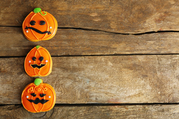 Creative cookies for Halloween party on wooden background, copy space