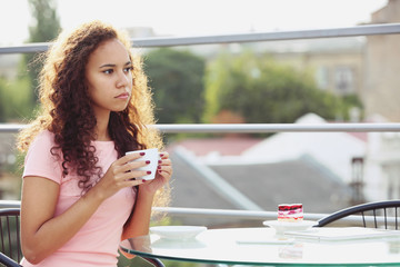 Pretty young woman in pink dress drinking coffee at summer terrace