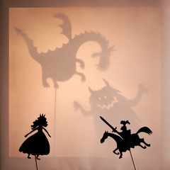 Shadow Puppets of Beautiful Princess and Brave Knight. Bright glowing screen of shadow theatre with monsters shadows in the background.