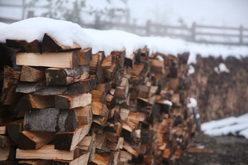 Logs of fire wood under snow