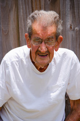 Portrait of a frail one hundred year old centenarian senior citizen man standing by a wooden fence