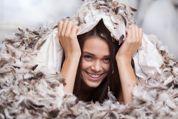 girl hiding under a duvet with feathers