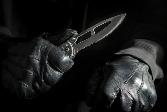 Assassin Holding Knife with Black Leather Gloves