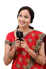 Happy traditional woman listening to music from a smart phone