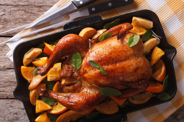 roasted chicken with oranges close-up in a pan. Horizontal top view