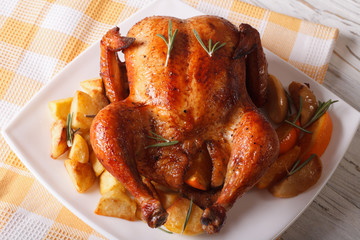 roast chicken with oranges, potatoes and apples close-up. horizontal