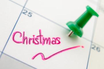 Pushpin on calendar with christmas.