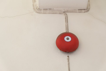 red fire alarm bell for warning security system mounted on wall