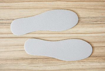 Shoe insoles on the wooden background