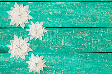 Origami snowflakes on old wooden background