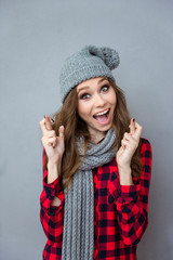 Amusing girl in scarf and hat smiling with crossed fingers