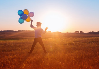 boy with balloons at sunset