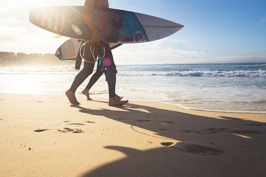 Australian surfers walking along Bondi Beach