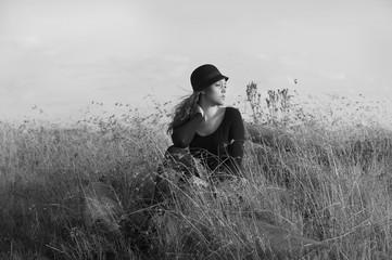 Monochrome portrait of lovely woman seated in field