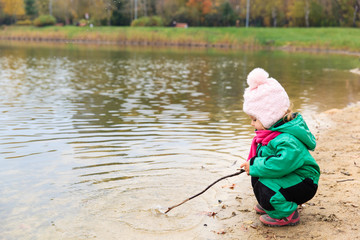 little girl playing with water and stick in autumn