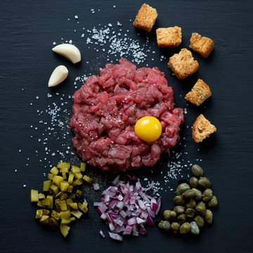 Beef steak tartare on a black wooden surface, top view, close-up