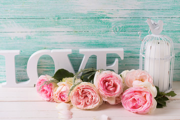 Background  with sweet pink roses flowers,  word love and candle