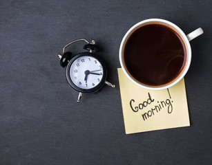 "Coffe, clock and paper with text ""Good morning"""