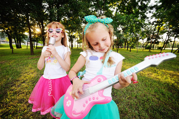 Two little girls play guitar and sing