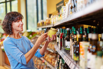 Frau scannt Honig im Supermarkt mit Handy