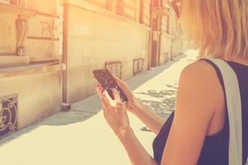 Urban girl using cellphone on a classic European street surroundings.