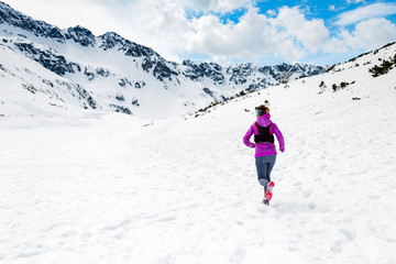 Happy woman winter trail running in beautiful inspirational land