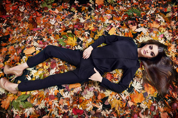Beautiful young sexy brunette girl with long silky hair evening makeup perfect figure dressed stylish fashion black silk pants suit blouse lying golden autumn leaves collection catalog cosmetic fall