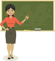 Smiling teacher holding pointer in front of blackboard