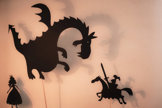 Shadow Puppets of Dragon, Princess and Knight with bright glowing screen of shadow theatre in the background.