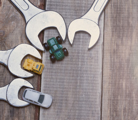 little toy cars near the wrenches on a wooden surface.metaphor for auto repair.top view.toned