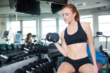 Pretty redhead woman lifting weights in gym