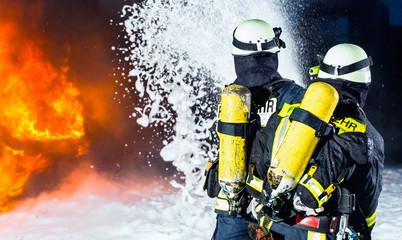 Feuerwehr - Feuerwehrmänner löschen ein großes Feuer, sie stehen vor einer Feuerwand und tragen Schutzkleidung