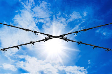 Barbed wire on blue sky background.