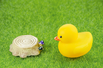 duck and tree stump toy on a grass