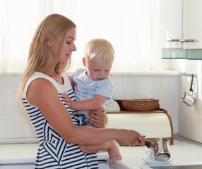 Woman making turkish coffee, holding child