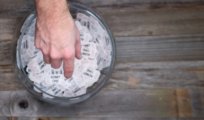 Reaching into a bowl of raffle tickets to find a winner
