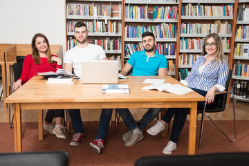 Group Of Students With Laptop In Library