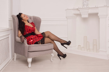 Attractive pin-up girl sitting on a chair