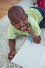 Smiling kid drawing pictures on paper