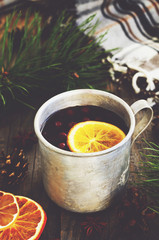 Winter drink with lemon and cranberries and cozy checked blanket