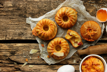 Muffins with cheese and bacon on a wooden background