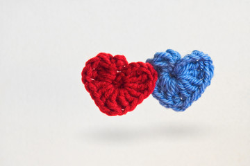 Two hand made crochet knit Red Heart and Blue Heart on white background. Valentines Day, Wedding composition with hearts.