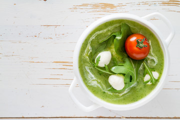 Arugula and tomatoes puree soup in white bowl