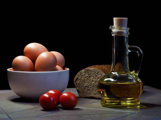 Ингредиенты для приготовления еды. Подсолнечное масло, помидоры, яйца, черный хлеб на столе, на черном фоне. Масло в красивой стеклянной бутылке. Помидоры маленькие, черри