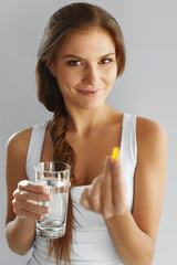 Nutrition. Healthy Lifestyle. Woman Holding Pill With Fish Oil O