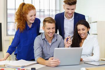 kollegen schauen lachen auf laptop im büro