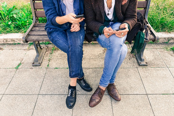 Couple of hipsters holding mobile phone - Two  trendy guys wifi connected sharing web content - Cropped human legs and hands with smartphone outdoors - Concept of modern business people taking a break