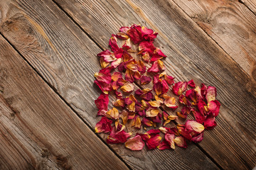 dried rose petals on wooden table