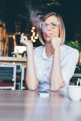 Woman smoking a cigarette in a cafe
