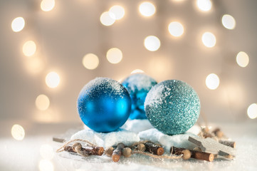 Christmas decoration with blue glass balls and  wooden elements. Lights in background. Shallow depth of field.